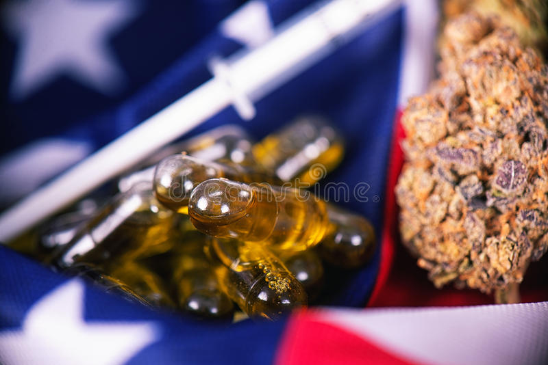 Detail of cannabis CBD oil capsules and bud in front of american royalty free stock photo