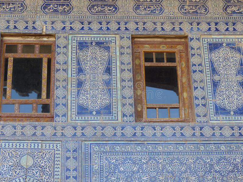 Detail of a ceramic decorated blue wall with two windows of an ancient madrasah of Khiva in Uzbekistan. Travel destination. Summertime and Holidaytime. Wood royalty free stock photography