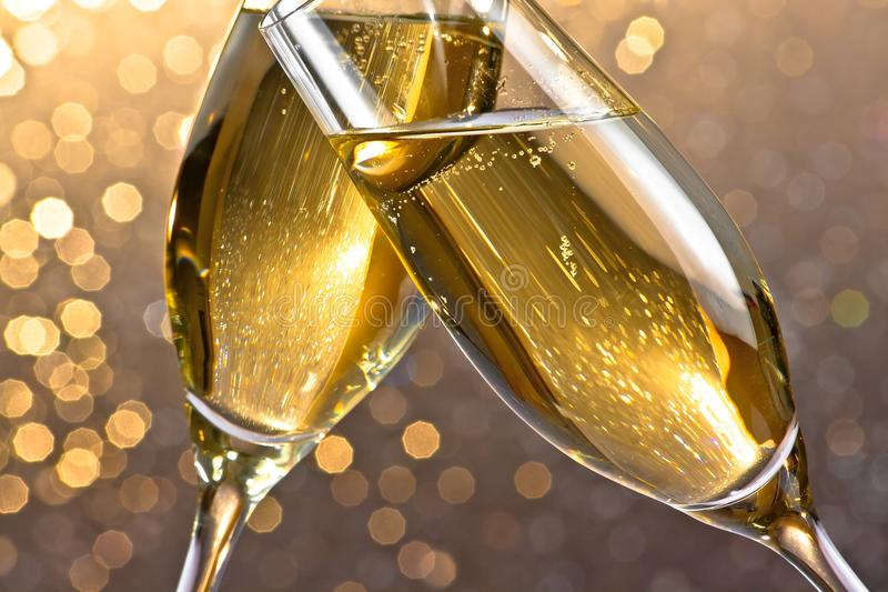 Detail of a champagne flutes with golden bubbles on light bokeh background. Detail of a champagne flutes with golden bubbles make cheers on light bokeh royalty free stock image