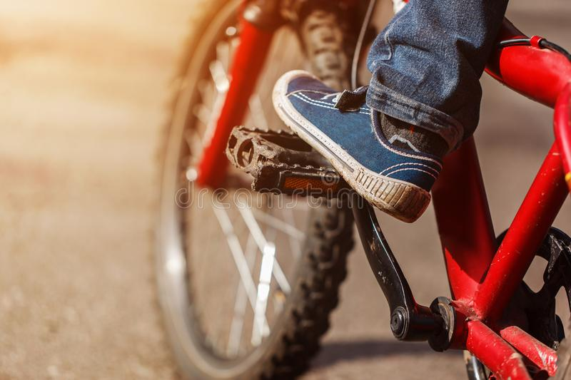 Detail of child cyclist feet riding bike on outdoor in sunny road. Closeup on pedal and foot stock image