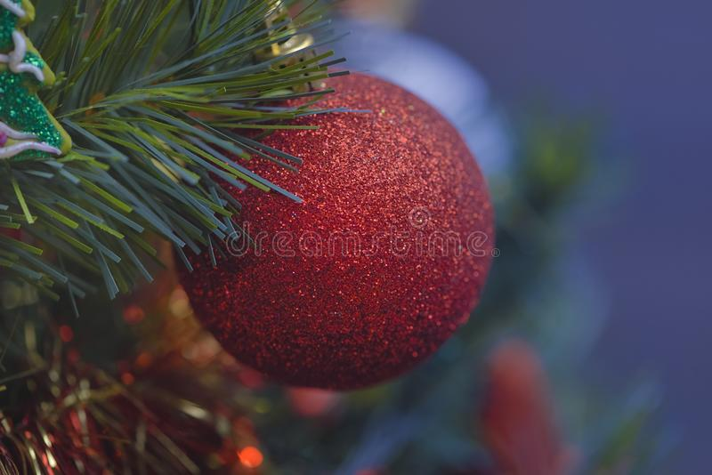 Detail of Christmas decoration on tree with coloured lights. Christmas tree in background royalty free stock photos