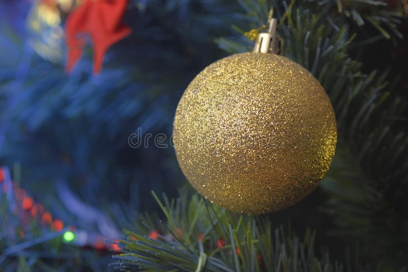 Detail of Christmas decoration on tree with coloured lights. Christmas tree in background stock photo