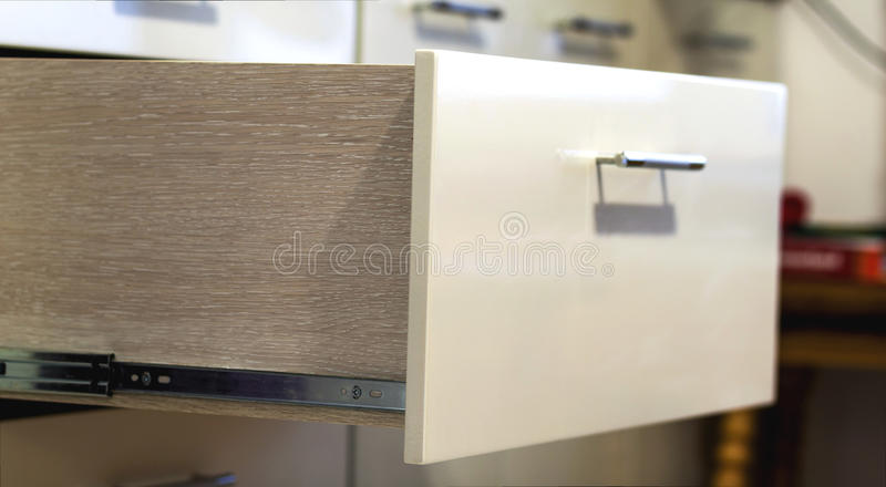 A detail close up shot of a laminate stylish kitchen drawer royalty free stock image