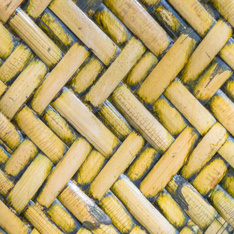 Detail close up view of a uniform golden woven basket using natural branch materials.Pattern of Thai style bamboo handcraft royalty free stock images