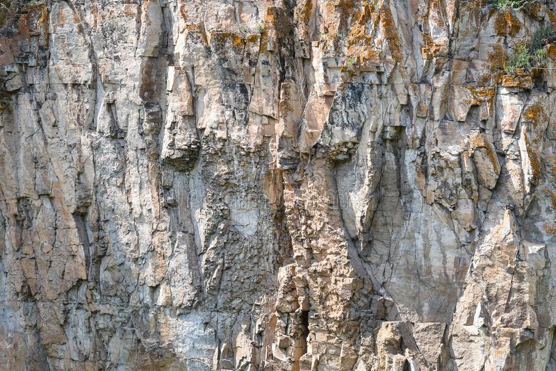 Detail closeup of a mountain rock wall, background or wallpaper of natural stone texture stock image