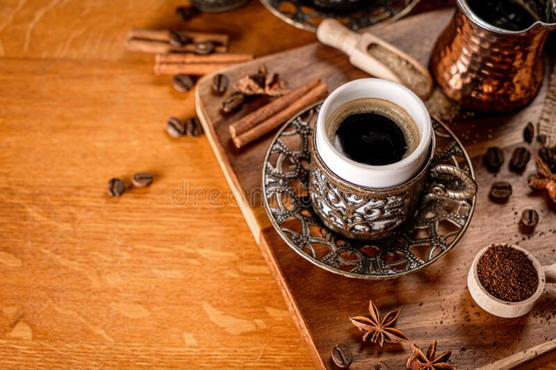 Detail of a coffee cup surrounded by coffee beans and spices on a natrual wood background stock image