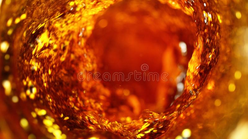 Detail of cola, tea or hard spirit beverages whirl. Abstract fresh drink background royalty free stock photography