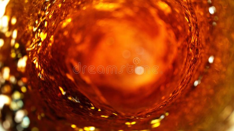 Detail of cola, tea or hard spirit beverages whirl. Abstract fresh drink background stock photo