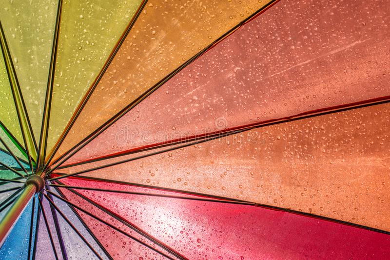 Colorful wet umbrella in the sunlight royalty free stock photography