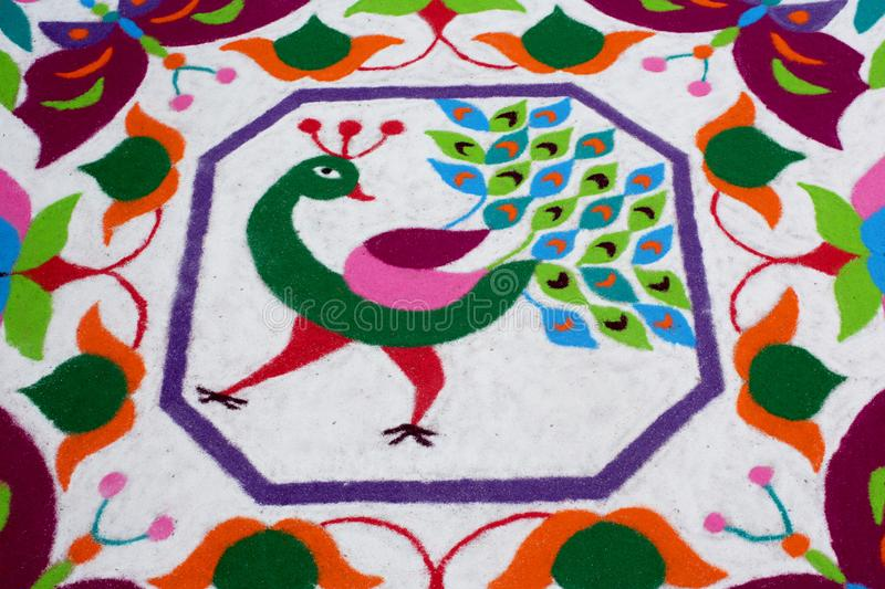 Colourful Rangoli Traditional Floral Design made with Dry Powdered Colours with Peacock, Flowers and Butterflies. Detail of a Colourful Rangoli Traditional royalty free stock image
