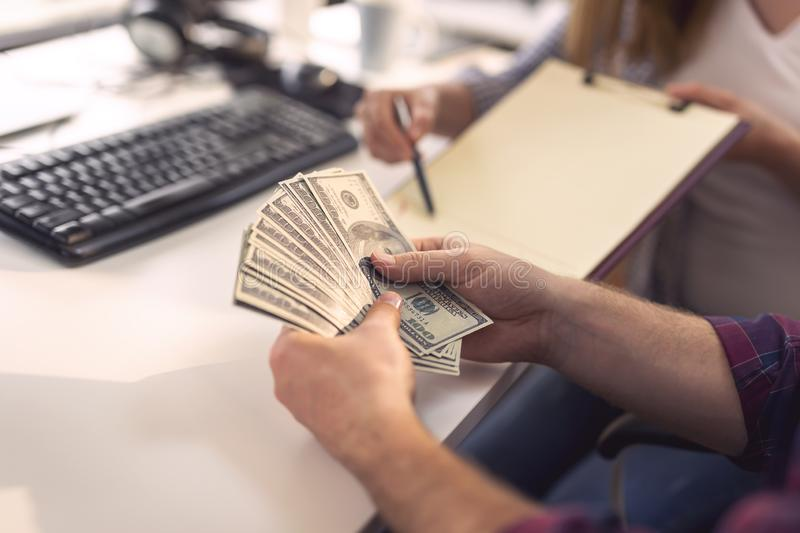 Corrupted businessman counting money. Detail of corrupted businessman counting bribery money offered to him in order to sign a contract. Selective focus stock image