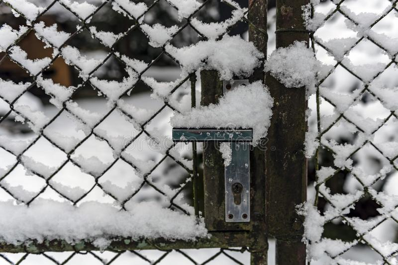 Detail of the crank of the garden gate covered with snow. In the winter landscape stock image