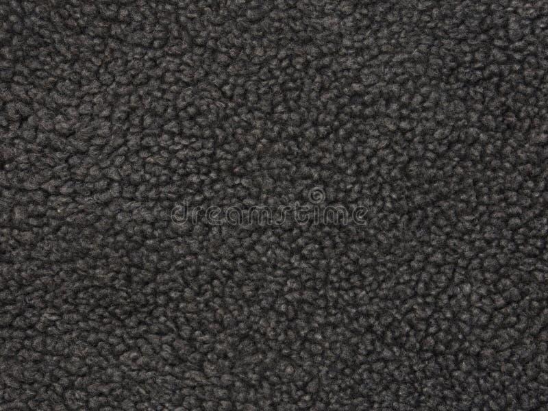 Dark Gray Fleece Material Up Close. Detail of a dark gray, wool-type fleece material is shown in a closeup view royalty free stock photos