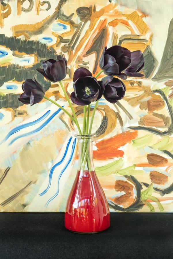 Detail Of Dark Purple Tulips In Flower Vase With Red Water And A