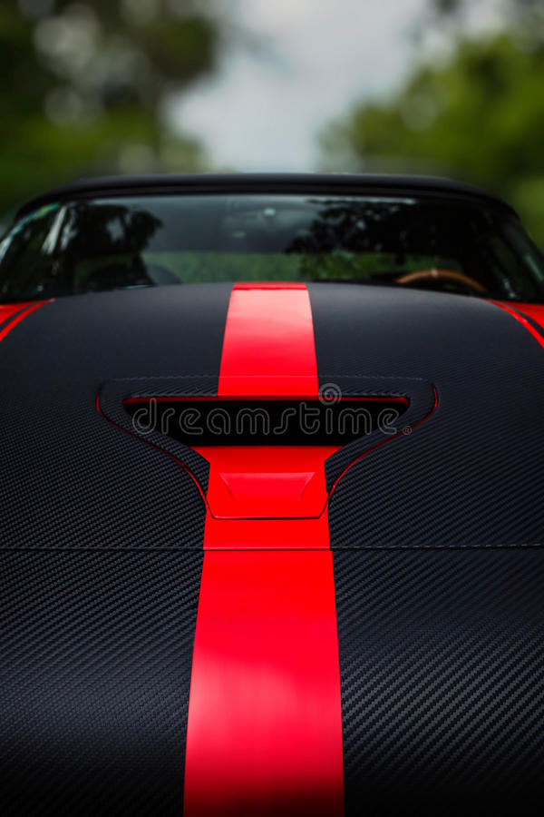 Detail of a dark racing sport car with bonnet scoop vent and red stripes royalty free stock photography