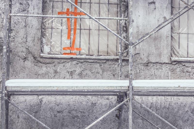 Detail der Altbauwand wieder aufgebaut im Winter - Kunststoffplatten auf Fenster, Gestellrohre bedeckt mit Schnee lizenzfreie stockfotos