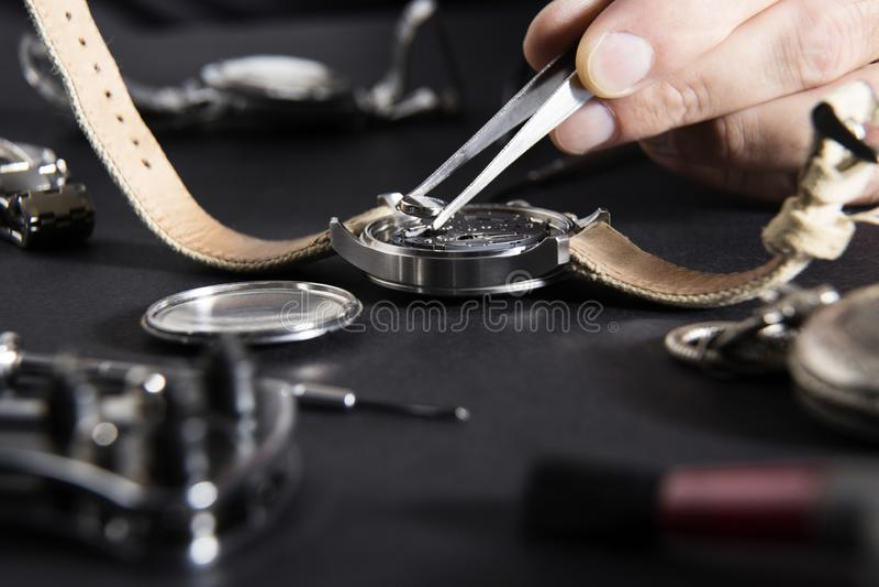 Detail der Arbeit eines Uhrmachers, der eine Batterie ersetzt lizenzfreie stockfotografie