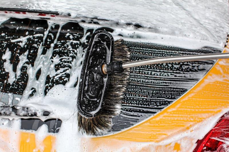 Detail der dunklen gelben Autoheckscheibe wusch sich im Autowäschen Bürste L lizenzfreie stockbilder