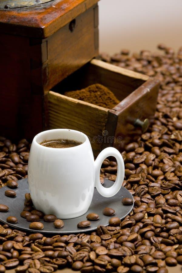 Detail der Kaffeemühle mit Kaffeebohnen und Tasse Kaffee lizenzfreie stockbilder