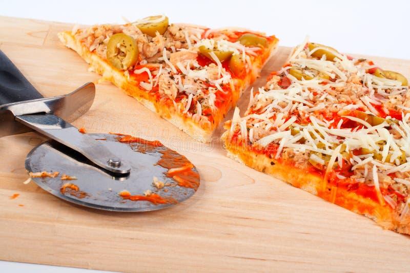 Detail der Scheiben italienische Pizza und Scherblock lizenzfreies stockbild