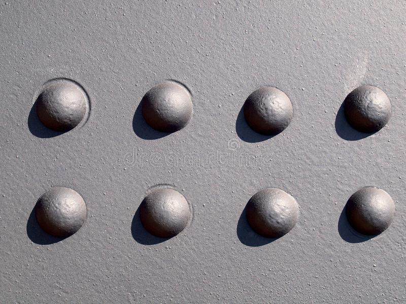 Detail der schwarzen Metallwand mit acht Nieten lizenzfreies stockbild