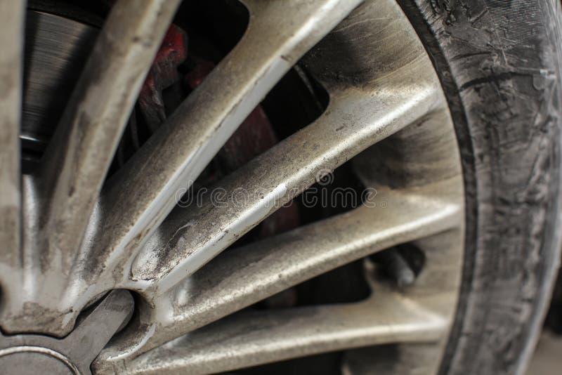 Detail der silberner Autokante und -reifens, sehr schmutzig vom Öl lizenzfreies stockfoto