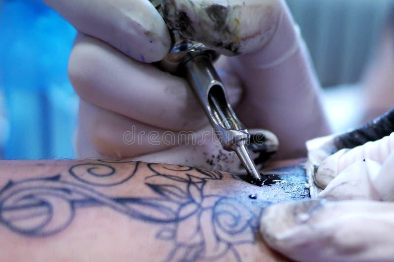 Detail der Tätowierungsherstellung - Tinte, Maschine und Hände in den Handschuhen stockbilder