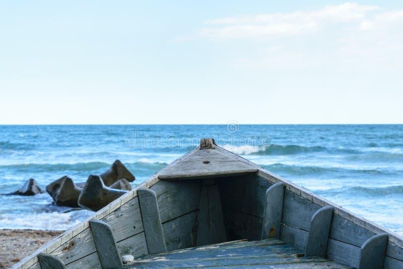 Detail des alten hölzernen Bootes auf Strandsand mit undeutlichem Meer des blauen Wassers im Hintergrund stockbilder