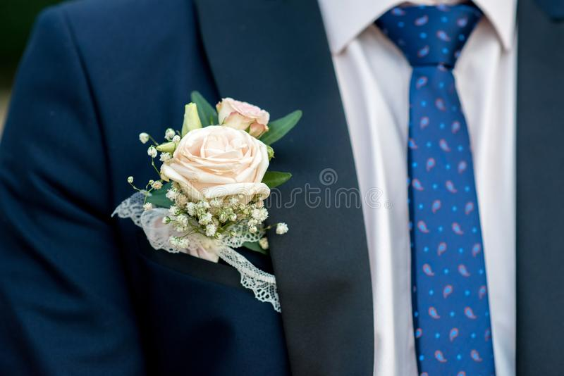 Detail des dunkelblauen Kostüms eines Bräutigams mit einem Knopfloch von Rosen lizenzfreie stockfotos