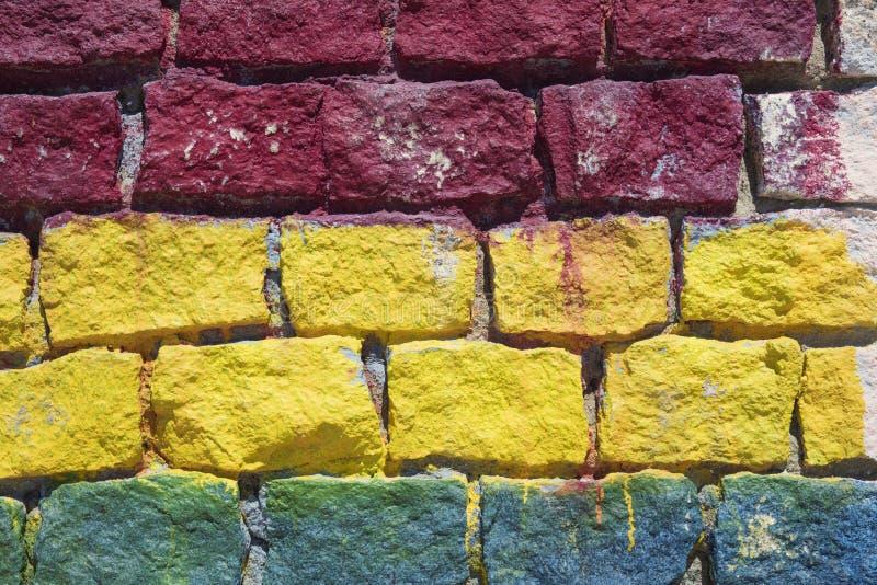 Detail des farbigen brickwall in Rotem, in Gelbem und in Blauem stockbild