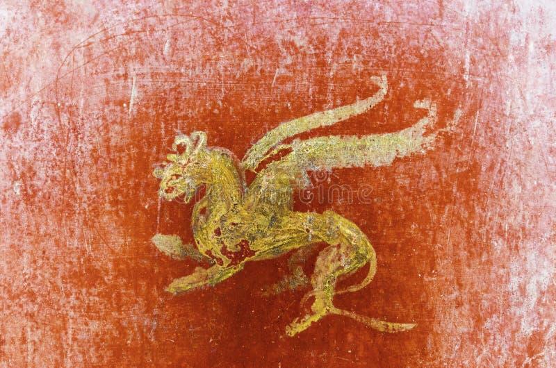Detail des Freskos in Pompeji mit geflügeltem Greif auf einem roten BAC stockbild