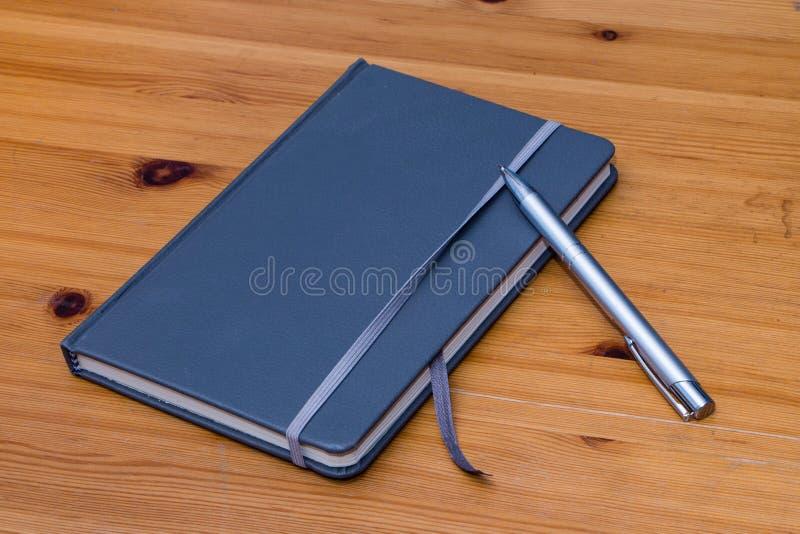 Detail des Notizbuches mit Stift auf dem hölzernen Hintergrund lizenzfreies stockbild