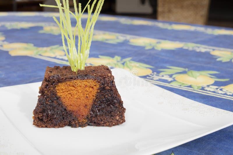 Detail des Ostern-Schokoladenkuchens mit Form der Karotte, als ob sie im Boden war stockbild