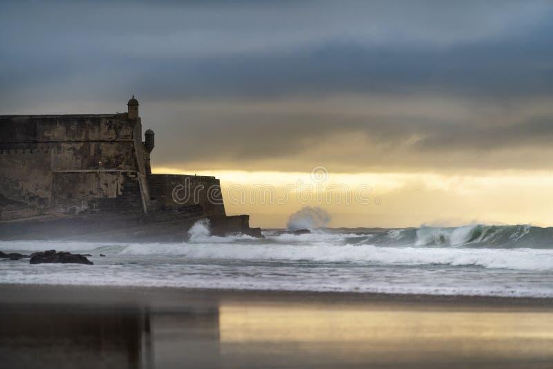 Detail des Sao Juliao da Barra Fort mit seiner Reflexion auf den Strand Sand und die Wellen in Carcavelos lizenzfreie stockfotos