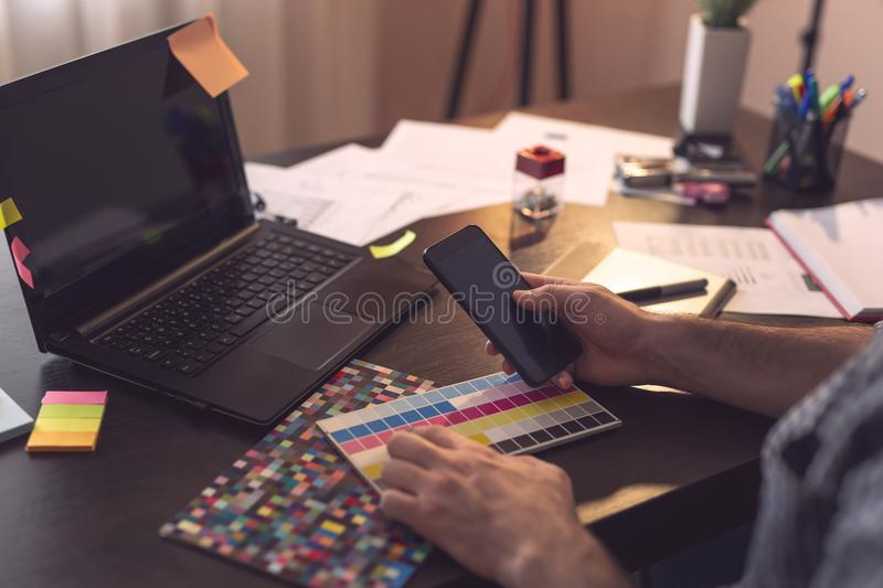 Graphic designer working. Detail of designer`s hands drawing using a drawing pad and choosing a color from a color palette. Focus on the thumb and the phone royalty free stock images