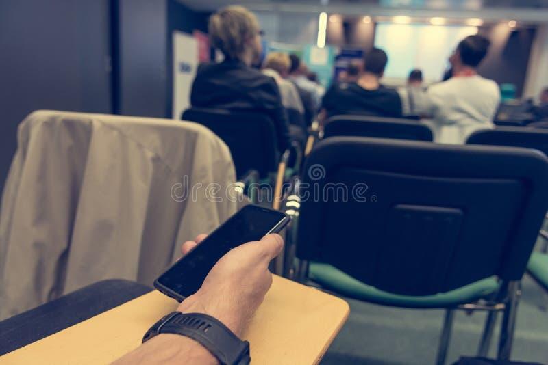 Detail die van zakenmanhand een smartphone houden op conferentie stock foto