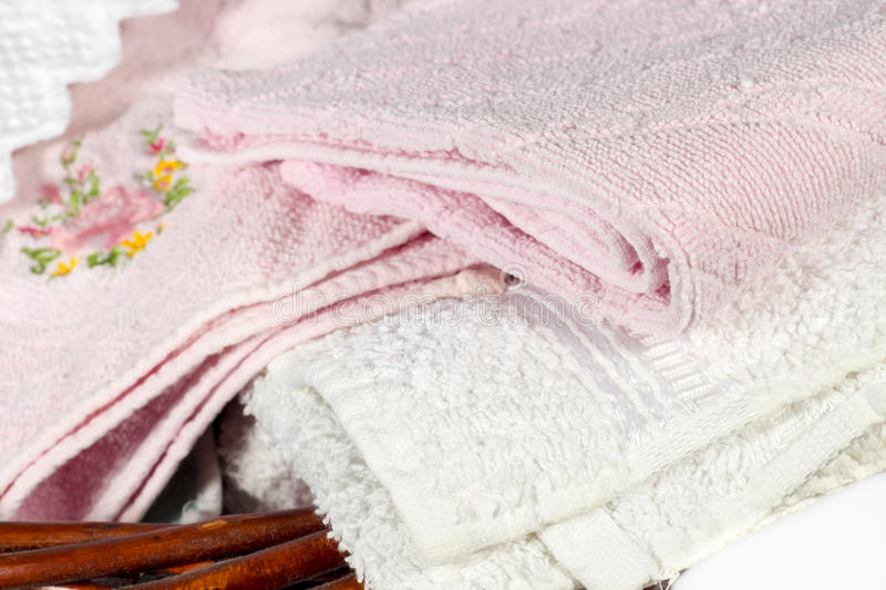 Detail of different hand towels on a wicker basket. Wicker basket for bathroom containing several hand towels of different colors and patterns. On white royalty free stock photography