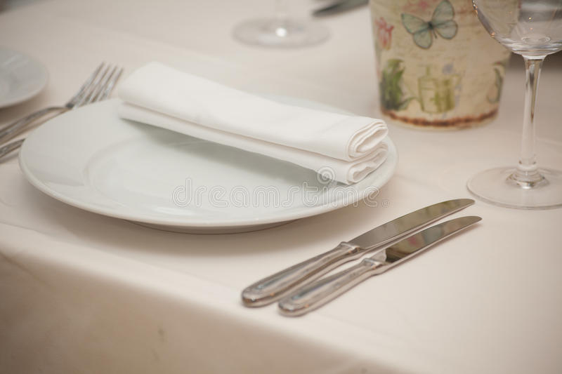 Detail of a dining table set up with wine glasses.  stock photo