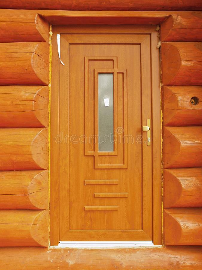 Detail of doors build in wooden beams cabin wall. stock photography