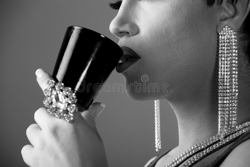 Detail of Drag queen. Detail shot of a Drag queen wearing lots of jewelry drinking from a wine glass royalty free stock photography
