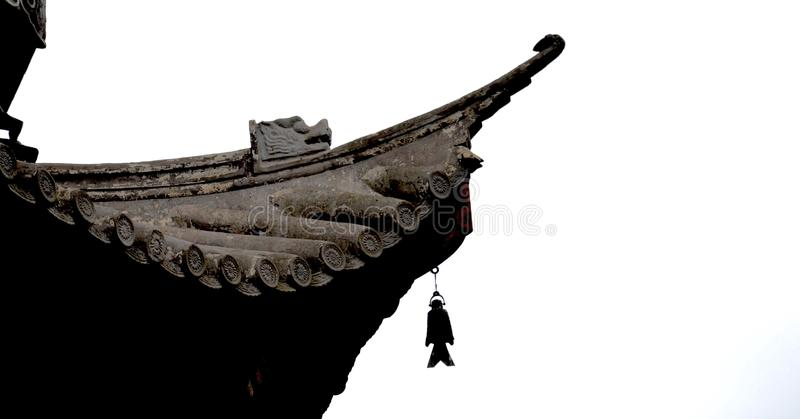 Detail of the edge of a roof on a Chinese pagoda, complete with dragon carving and fish shaped bell royalty free stock photography