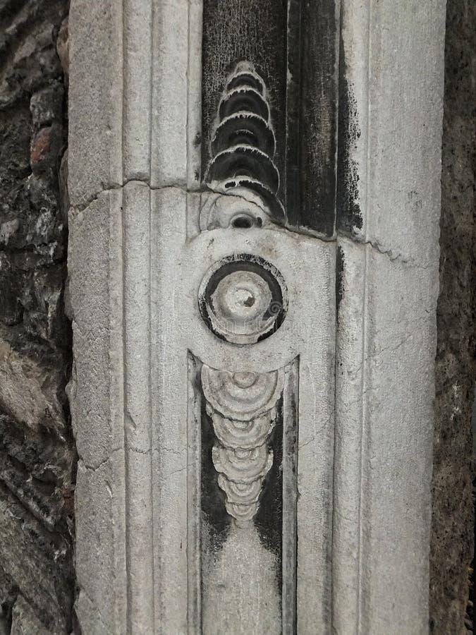 Detail einer Ecke einer äußeren Wand in einer Straße von Como, Italien Weißer zeit-verwitterter Stein, gebrochen und mit Ruß teil stockfotografie