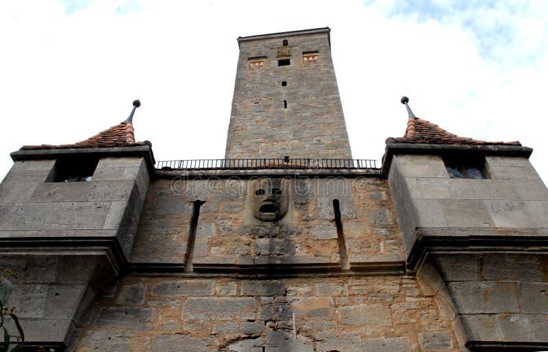 Detail eines Altbaus mit Steinmaske und des alten Turms in der Stadt von Rothenburg in Deutschland stockbild