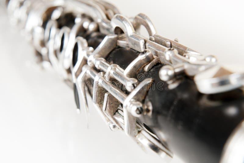 Detail eines alten schwarzen Clarinet auf weißem Hintergrund stockfotografie