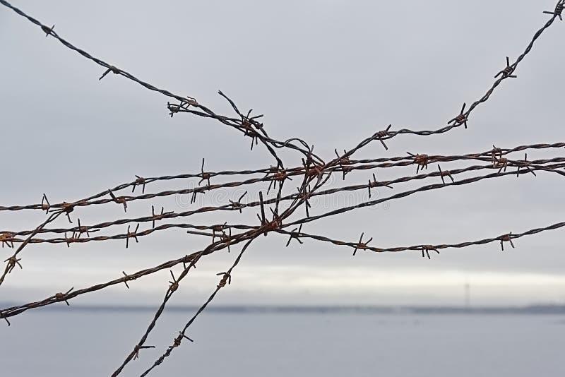 Detail eines zerbrochenen Zaunes mit Stacheldraht, mit Meer und Küste im Hintergrund lizenzfreies stockbild