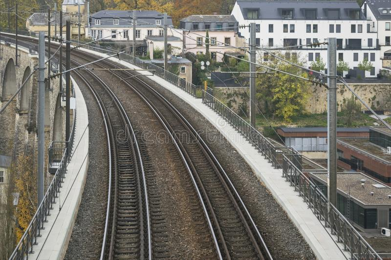 Detail of electrical railroad in Luxembourg city with rails, contact lines and viaduct structures. In dark autumn day illustrating urban transport concept stock photography