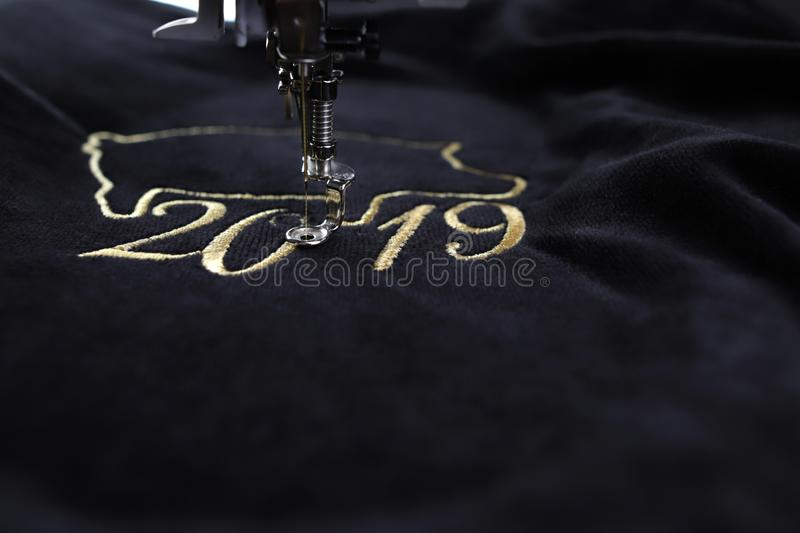 Detail of embroidery machine stitching 2019 chinese new year motive with precious gold yarn on black velvet royalty free stock images