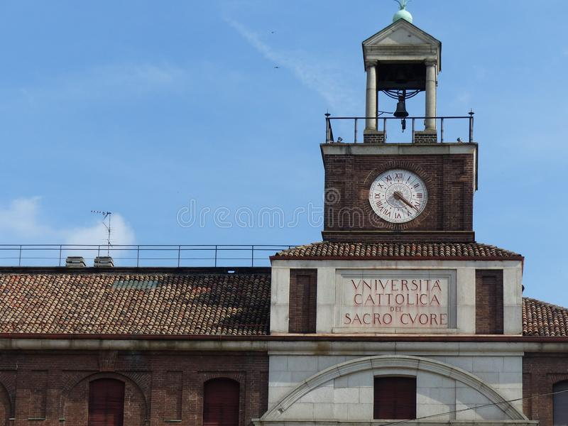 Detail of the entrance of the Catholic University in Milan with a clock. Italy. royalty free stock photography
