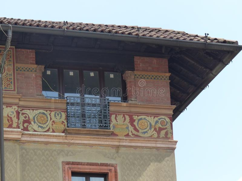 Detail of the extremity of an angle of a house with some frescos in the historical center of Milan in Italy. Long windows. Multicolored frescos. Paintings of royalty free stock photography
