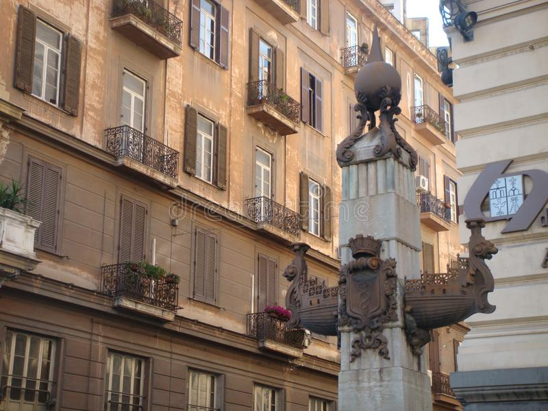 Detail of the extremity of a column with in the center a statue of an ancient vessel in Naples Italy. stock image